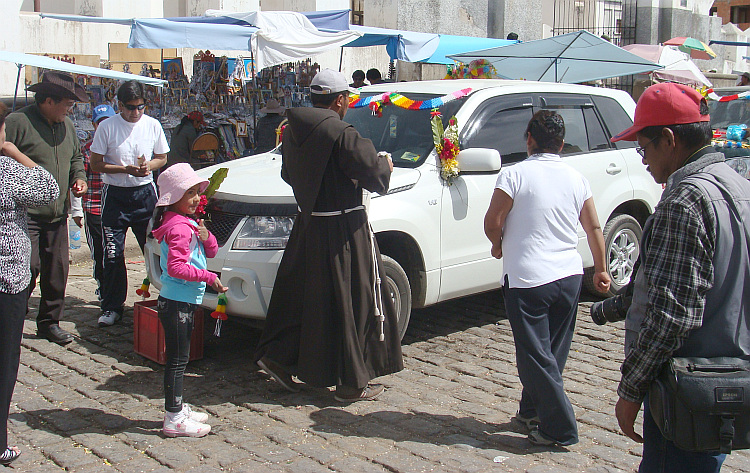 The priest is blessing the cars